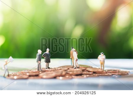 Tiny miniature models of businessman are standing on a pile of coins using as agreement investment achievement and partnership business concept.