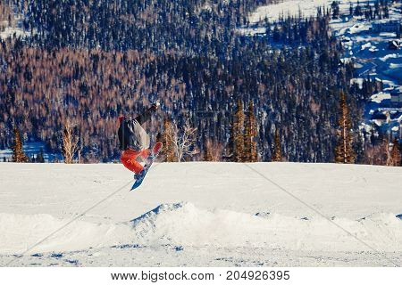 Snowboarder in flight and jumping, shows tricks.
