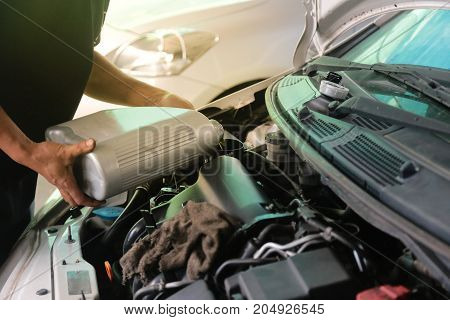 The car mechanic is filling up the engine oil to the customers' car in his car repair shop. Change engine oil in garage shop.