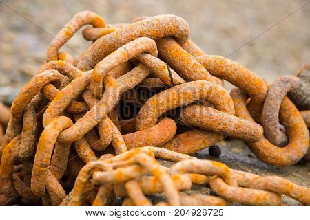 Old orangy rusty heavy iron chain, close-up