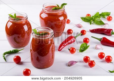 Tomato ketchup sauce with cherry tomatoes and red hot chili peppers, garlic and herbs in a  glass jar on white background. Homemade tomato sauce and fresh tomatoes.