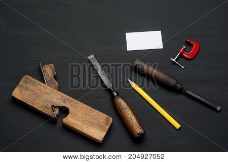 Joinery tools on dark wooden table background with blank business card.