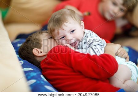 Little kid boy hugging with newborn baby girl, cute sister. Siblings. Brother on background. Kids bonding. Family of three bonding, love.