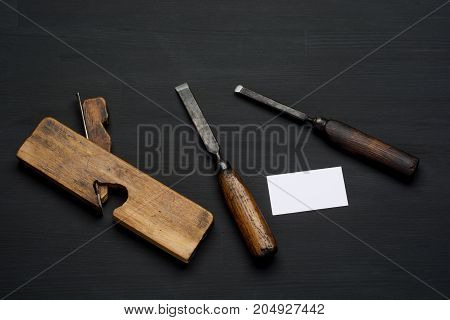 Woodworking tool on dark wooden background. chisel, plane and empty business card