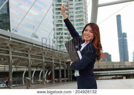 Portrait of cheerful Asian businesswoman looking confident and smiling in the city background. Successfull business concept.