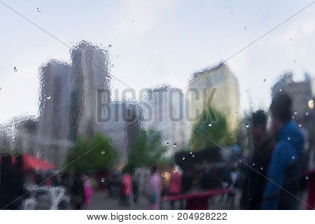 Rainy day in city. Selective focus on the raindrops. Distorted reflection of city and people on metal surface,