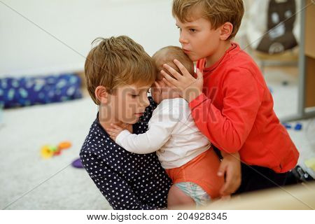 Two little kid boys hugging with newborn baby girl, cute sister. Siblings. Brother and adorable baby playing together. Kids bonding. Family of three bonding, love.