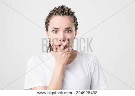 Indoor shot of cute caucasian girl with braids looking at camera, having doubtful and indecisive face expression, closing her lips as if forbidden to say anything. Confused young female posing