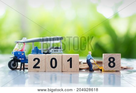 Workers are transferring or pulling a wooden number 8 to link with number 2018 with auto rickshaw (named in Thai