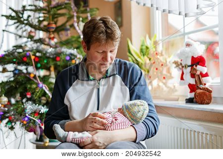 Happy proud young father holding his sleeping newborn baby daughter on arms with Christmas tree on background. Dad with baby girl, love. New born child sleeping in dad arms. Bonding, family, new life