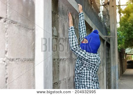 Robber in a mask climbing through a fence