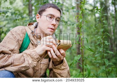 Picture of biologist man in glasses with notebook and pencil in woods among plants and trees in summer day