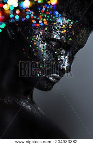 Creative Female Portrait. Face In Black Paint With Large Sequins