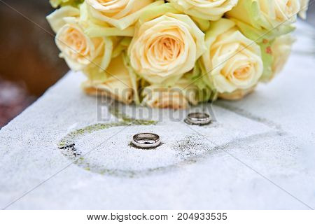 Wedding flowers and rings on frozen surface