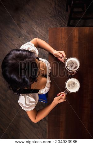 Oktoberfest. Brunette woman holding beer mugs in bar. Sexy woman holding two glasses of beer standing at the bar counter. Top view