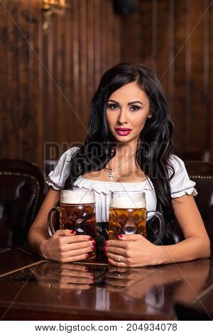 Woman wearing a traditional Bavarian dress dirndl posing with a beer mugs at bar. Sexy brunette sitting at the table in a bar. Octoberfest