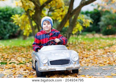 Little preschool kid boy driving big toy old vintage toy car and having fun, outdoors on beautiful autumn day. Active leisure with children in fall park with yellow foliage