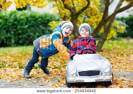 Two happy twins kids boys having fun and playing with big old toy car in autumn garden, outdoors. Brother pushing car for child. Happiness, fun, leisure in fall park. Children driving race car