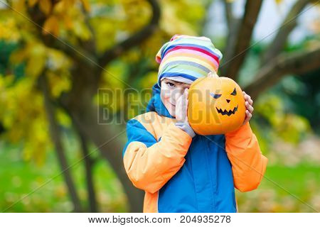Happy cute little kid boy with halloween pumpkin lantern. Funny child in colorful clothes having fun and playing in autumn garden on cold autumnal day. Scary jack-o-lantern, celebration of holiday