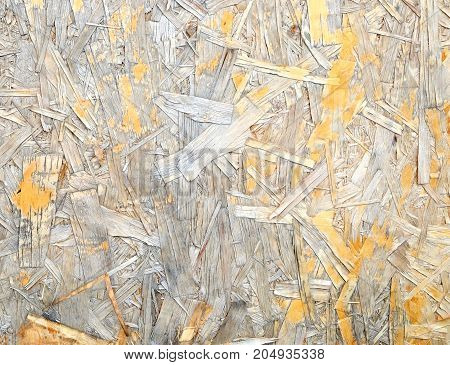2) Weather damaged Oriented Strand Board. Construction material. OSB wooden panel made of pressed sandy brown wood shavings as background closeup