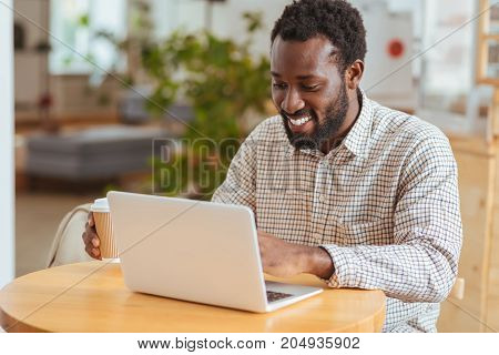 Inspired IT specialist. Charming cheerful man sitting at the table in the cafe and developing a new application on his laptop while holding a cup of coffee