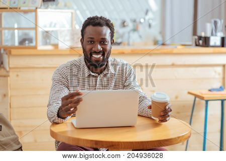 Necessary adjustment. Charming young man sitting at the table, holding a cup of coffee and changing the angle of the laptop screen while smiling at the camera