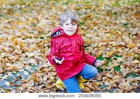 Portrait of happy cute little kid boy in red rain coat and yellow rubber boots with autumn leaves background. Funny child having fun and playing in fall forest or park on cold autumnal day.