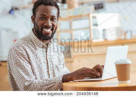 Business correspondence. Charming smiling man sitting at the table in the cafe and typing an e-mail while smiling at the camera
