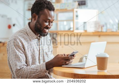 Good news. Charming cheerful man sitting at the table in the cafe and reading a text message from his friends while smiling happily