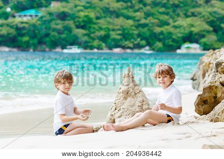 Two little kids boys having fun with building a sand castle on tropical beach of Seychelles. children playing together on their vacations.