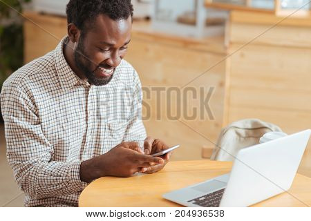 Fun chat. Handsome upbeat man sitting at the table in the coffee house and texting his friends on the phone while laughing