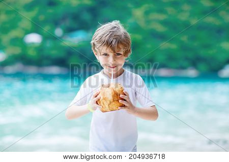 Happy funny little preschool kid boy drinking coconut juice on ocean beach. child playing on family vacations on tropical island. summer, happiness, childhood concept