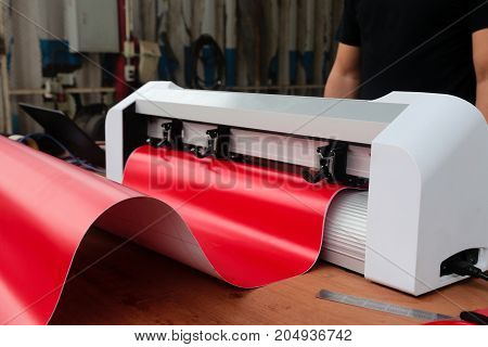 Sticker machine and red sticker sheet ready to cutting stickers for use different types of jobs.