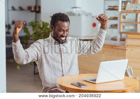 Long-awaited success. Happy young man sitting at the table in the coffee shop and raising hands in celebration after his program starts working successfully