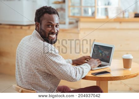 Work brings pleasure. Happy cheerful man sitting at the table in the cafe and developing a presentation about global trading transfers on the laptop while smiling at camera