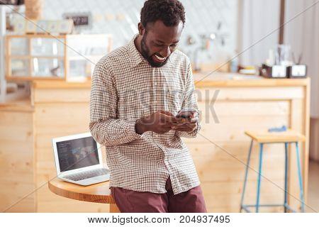 Mood-boosting chats. Cheerful pleasant young man leaning on the table in the cafe and sending text messages to his friends via his phone while smiling happily