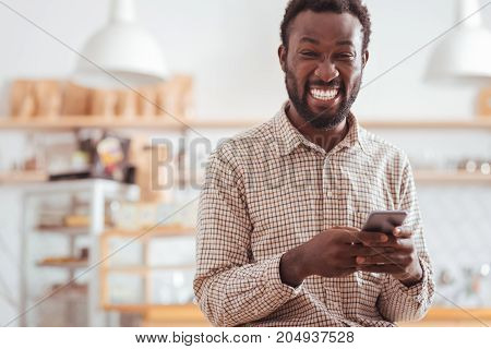 Hilarious messages. Overjoyed upbeat young man standing in the coffee house and laughing hard while reading funny text messages from his friends on his phone