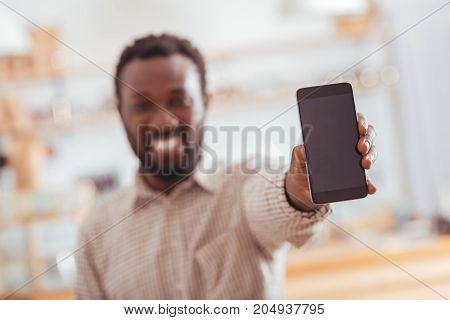 Brand-new device. The focus being on the phone in the hands of a cheerful young man smiling broadly, being happy about his new purchase