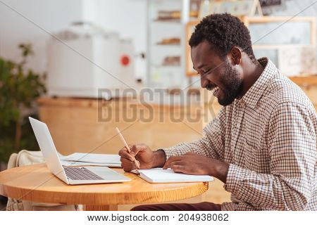 Planning the day. Cheerful young man sitting at the table in the cafe and making notes in his daily planner, deciding upon his agenda while smiling broadly