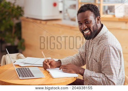 Love my work. Happy young man sitting at the table in the coffeehouse, making notes in his notebook and smiling at the camera broadly