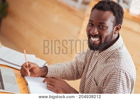 Inspired worker. Cheerful smiling young man sitting at the table in the cafe and posing for the camera while making notes in his notebook