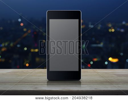 Modern smart phone with blank grey screen on wooden table over blur night light of city tower background