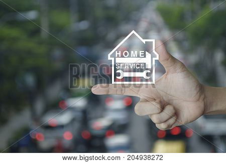 Hammer and wrench with house icon on finger over blur of rush hour with cars and road Home service concept