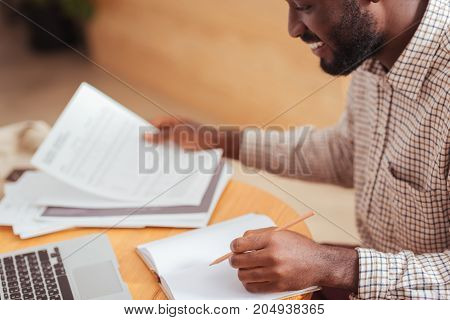 Happy to work. Pleasant upbeat young man sitting at the table in a coffeehouse and working with documents, making notes in the notebook while smiling