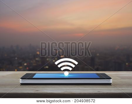 wi-fi button flat icon on modern smart phone screen on wooden table over blur of cityscape on warm light sundown Technology and internet concept