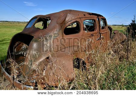 Frame of a old rusty car  missing a trunk lid and wheels