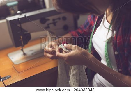 Young seamstress making some repairs manually sewing in buttons on a shirt. Focus on the button