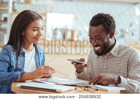 Cheerful ambience. Charming young man taking a photo of documents and discussing them with his pretty female colleague in the coffeehouse while both smiling
