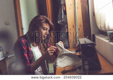 Young seamstress making some repairs manually sewing in buttons on a shirt. Focus on the needle