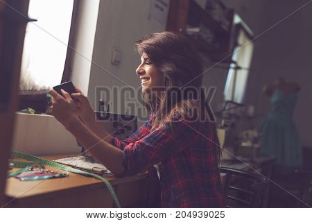 Young fashion designer holding a smart phone surfing the net in search for fresh design ideas